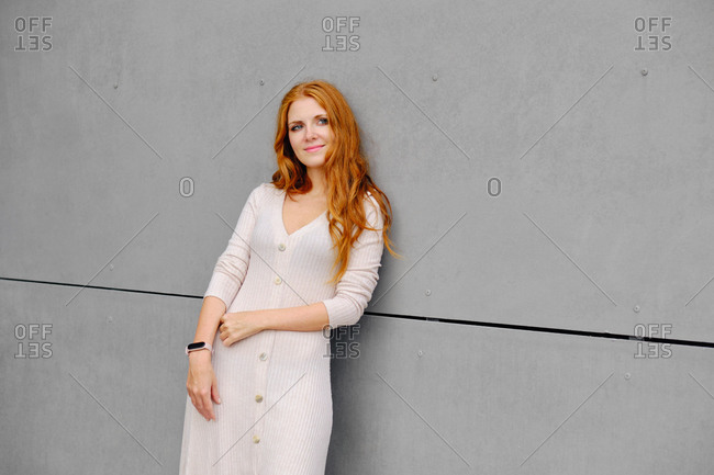Positive young female with long red hair wearing casual dress and smart bracelet looking away while standing against concrete wall