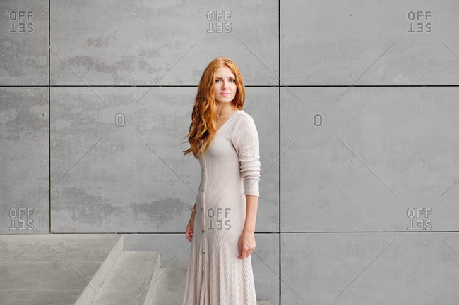 Positive young female with long red hair wearing casual dress and looking at camera while standing against concrete wall