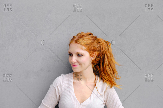 Positive young female with long red hair wearing casual dress and looking away while standing against concrete wall