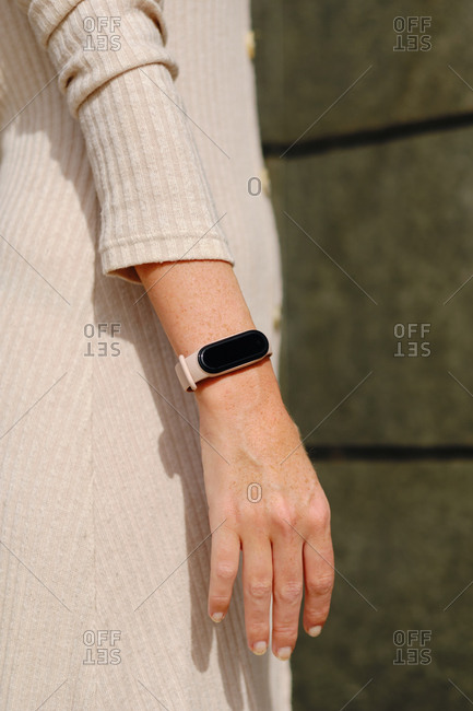 Side view of crop unrecognizable modern lady in elegant beige dress and with smart bracelet on wrist