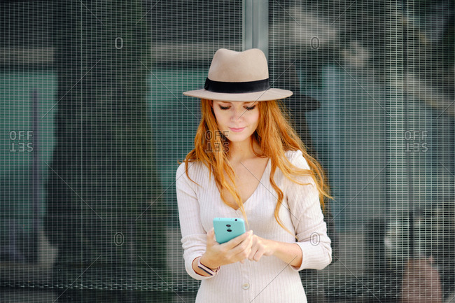 Young elegant redhead female in stylish outfit and hat browsing mobile phone while standing near glass wall of modern urban building
