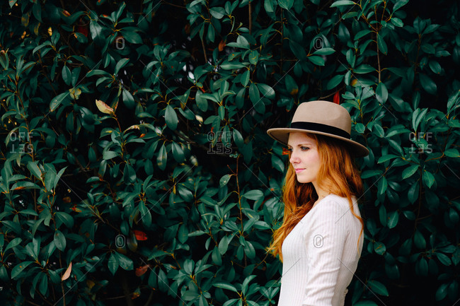 Attractive young long haired ginger female in stylish hat looking away while standing against green bushes in summer garden
