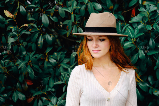 Attractive young long haired ginger female in stylish hat looking down while standing against green bushes in summer garden