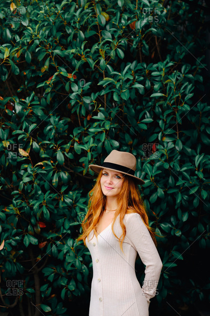 Attractive young long haired ginger female in stylish hat looking at camera while standing against green bushes in summer garden