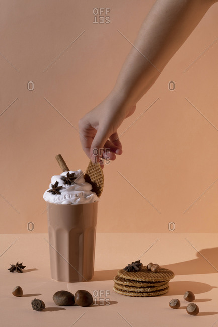 Glass with chocolate cocktail with whipped cream garnished with star anise and cinnamon stick placed on table with hazelnuts and cookies on pastel brown background