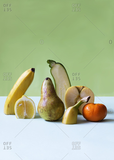 Composition of various fruits cut in halves and arranged on table on green background in studio