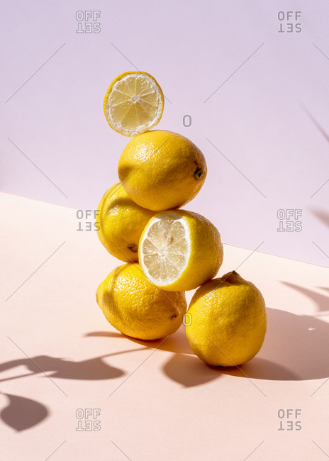 Creative composition of fresh lemons stacked in shape of pyramid on pink background in studio