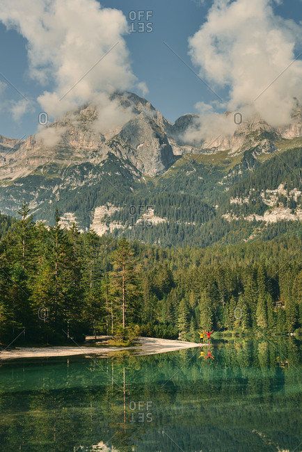 Picturesque view of calm clear pond surrounded by evergreen woods and high Dolomites mountains located in Italy