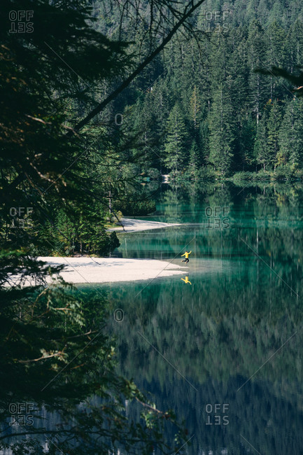From above of anonymous traveler jumping close to tranquil lake with bright water surrounded by green forest in Italy