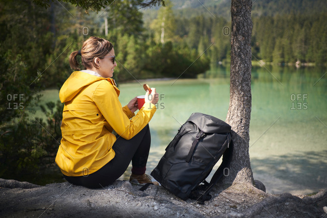 Back view of happy female backpacker smiling while having rest on shore of lake during trip in nature in Italy