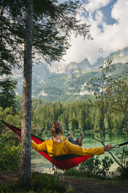 Back view full length of unrecognizable traveler relaxing in hammock and enjoying landscape of Dolomites mountains and lake
