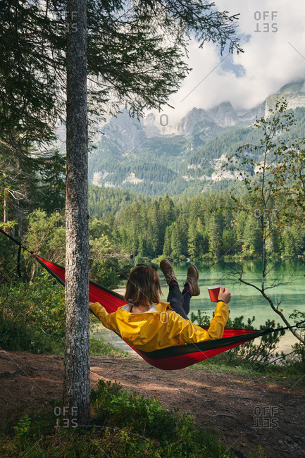 Back view full body of unrecognizable female tourist swinging in hammock with cup of drink and admiring view of lake and mountains in Italy