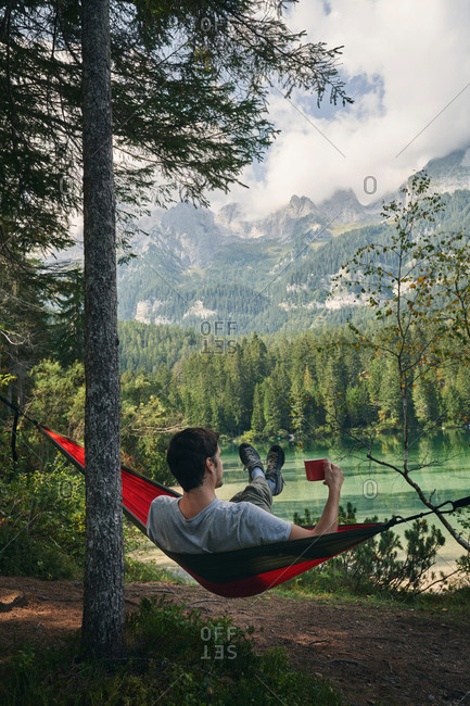 Back view full length of unrecognizable traveler relaxing with a cup in hand in hammock and enjoying landscape of Dolomites mountains and lake