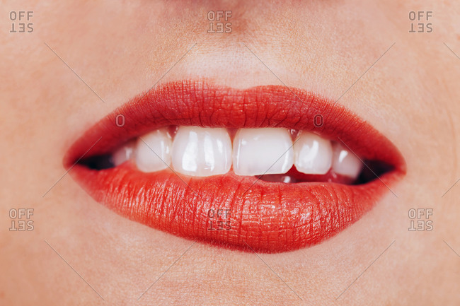 Cropped unrecognizable woman with perfect teeth seductively biting red lips