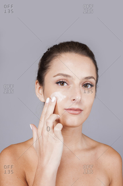 Young beautiful woman with healthy skin taking care of face with cream isolated on gray background looking at camera