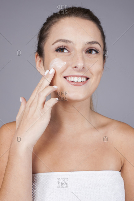 Young happy beautiful woman with healthy skin taking care of face with cream isolated on gray background looking away