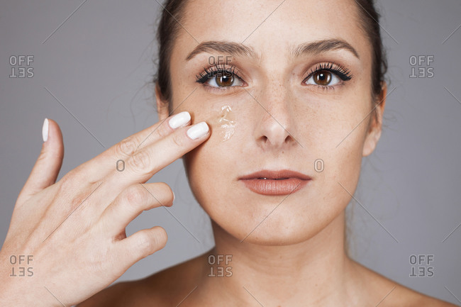 Young beautiful woman with healthy skin taking care of face with foundation isolated on gray background looking at camera