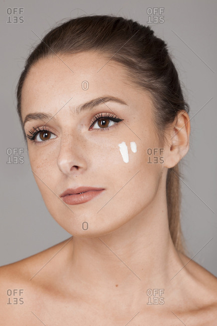 Young beautiful woman with healthy skin taking care of face with cream isolated on gray background looking away