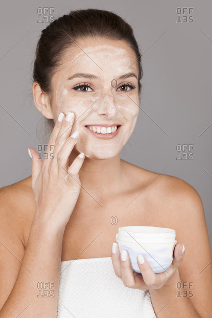 Content woman using nourishing cream from pot on hand and looking at camera isolated on gray background