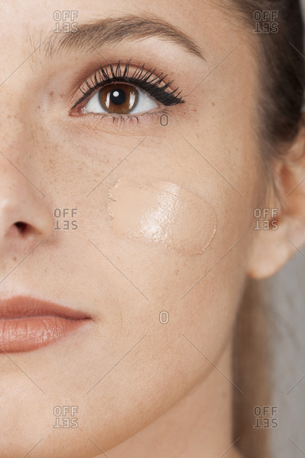 Young beautiful woman with healthy skin taking care of face with foundation isolated on gray background looking away