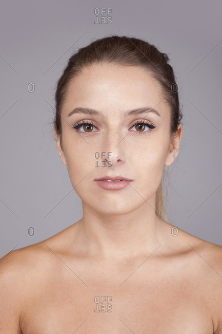 Young beautiful woman with healthy skin isolated on gray background looking at camera