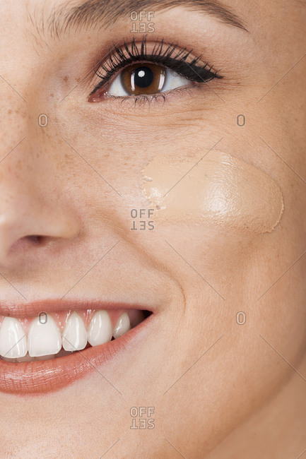 Young happy beautiful woman with healthy skin taking care of face with foundation isolated on gray background looking away