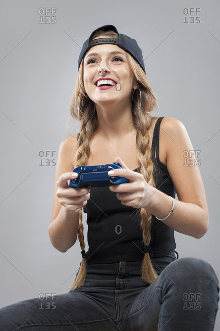 Cheerful young woman in hat and pigtail hairstyle playing console with joystick on gray background looking away