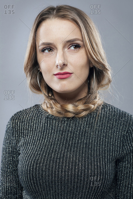 Unemotional female model with braided hairstyle and in casual clothes standing on gray background in studio and looking away