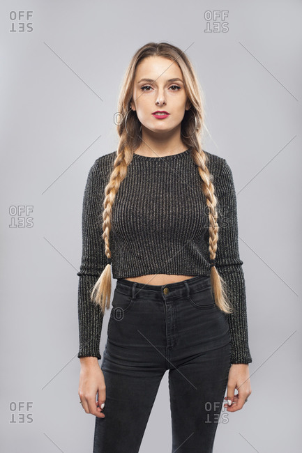 Charming female in casual wear and with long braids standing on gray background in studio looking at camera