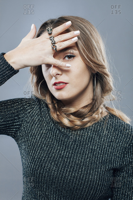 Unemotional female model with braided hairstyle and in casual clothes covering face with hand on gray background in studio and looking at camera
