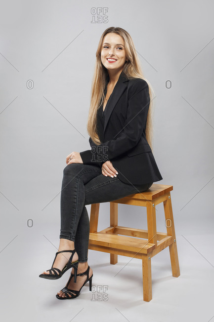 Side view of charming female model in smart casual style sitting on wooden stool on gray background and looking away