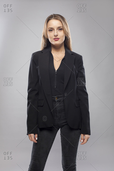 Happy female teacher in formal jacket standing on gray background in studio and pondering while looking at camera