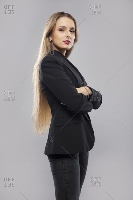 Side view of happy female teacher in formal jacket standing on gray background in studio and pondering while looking at camera