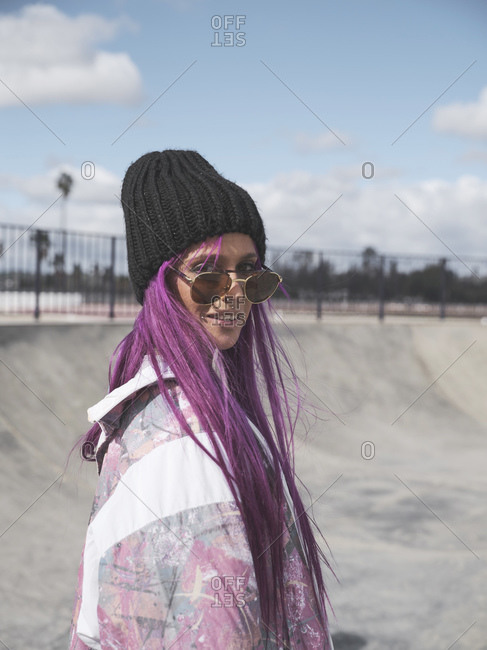 Delighted female in trendy street style outfit and with vivid dyed hair riding roller skates in skate park in summer while looking at camera