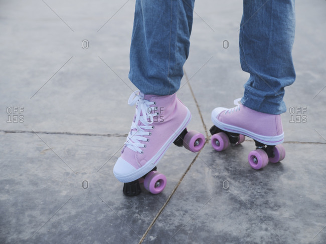 Side view of unrecognizable female wearing trendy jeans standing in pink roller skates in urban skate park