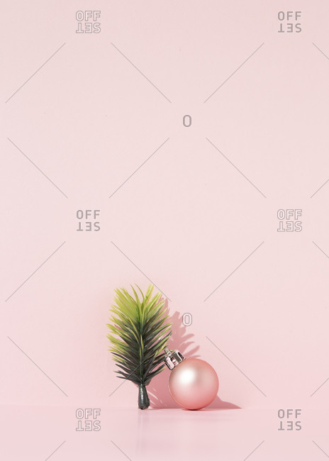Decorative spruce branch and shiny Christmas ball arranged on pink  background in studio