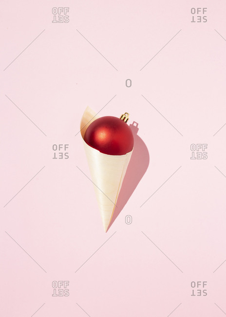 Top view of red shiny Christmas ball in paper cone in shape of ice cream placed on pink background