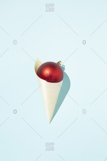 Top view of red shiny Christmas ball in paper cone in shape of ice cream placed on blue background