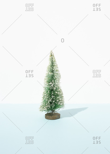 Miniature of decorative Christmas tree placed on table in studio on blue background