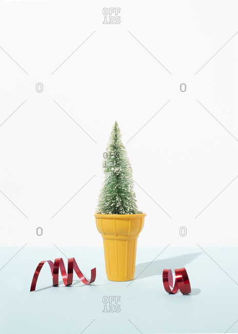 Miniature Christmas tree in decorative ice cream cup placed on table with red shiny ribbons in studio on blue background