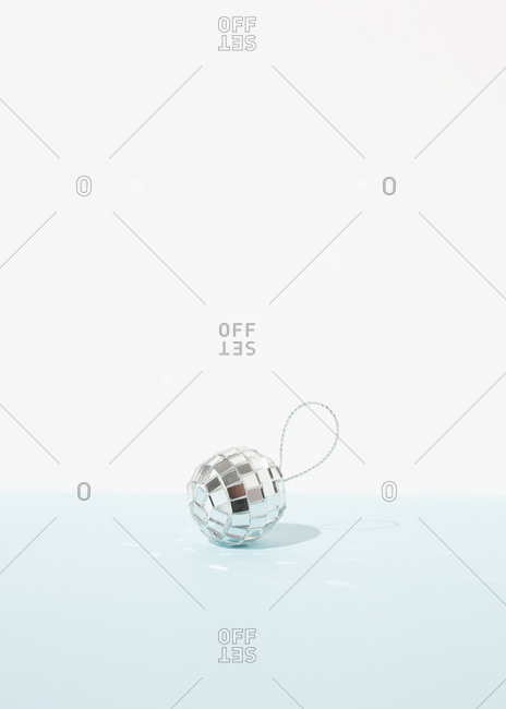 Miniature glowing disco ball placed on table as Christmas decoration on blue background