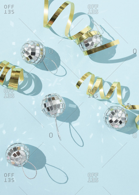 Shiny Christmas baubles in shape of disco balls placed on blue background in studio