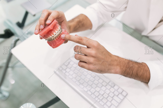 Dentist's hand with aesthetic orthodontics seen from above