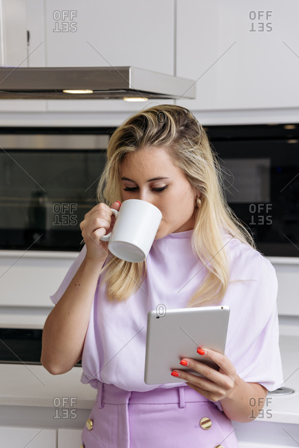 Female standing in kitchen and drinking fresh morning coffee while reading news on tablet in morning and having breakfast