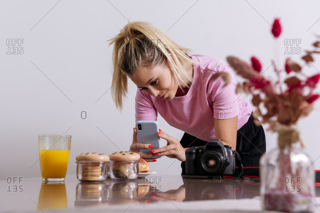 Female photographer taking picture of desserts and glass of orange juice with smartphone while working remotely from home