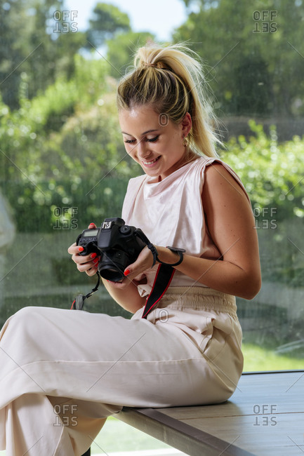 Side view of cheerful professional female photographer sitting on table and looking through pictures from photo session after working day