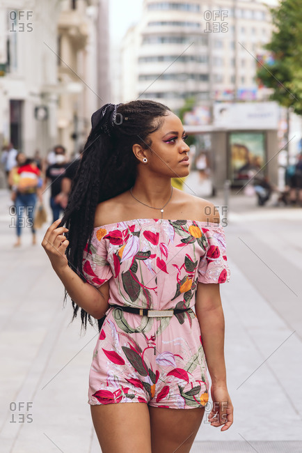 Young black lady in stylish clothes with Afro braids looking away in city