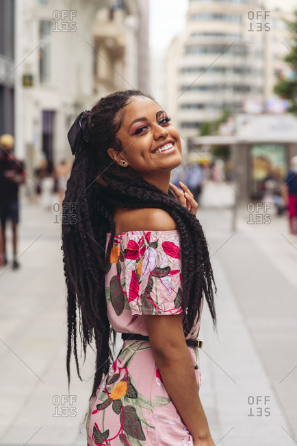 Side view of young happy black lady in stylish clothes with Afro braids looking at camera in city