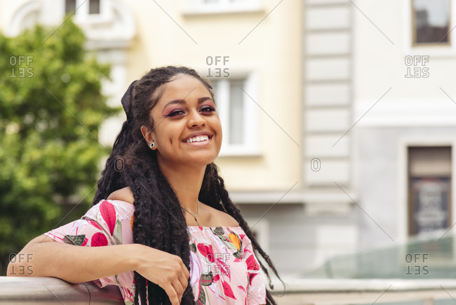 Side view of young cheerful ethnic female in ornamental apparel leaning on metal fence on street while looking at camera