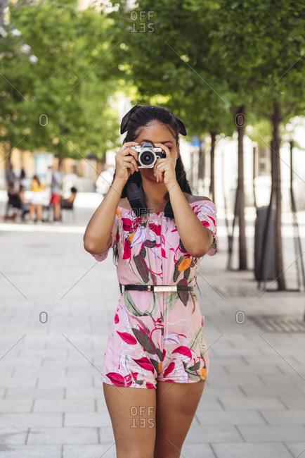 Unrecognizable trendy female in ornamental wear taking photo on digital camera on city street
